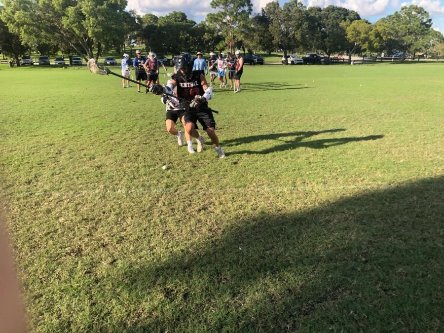 Matteo Darquea and Myles Medina reach for a ground ball during their lacrosse practice. With the pandemic, most teams are facing new restrictions and uncertainty over college recruiting.