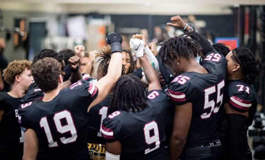 Bronco Varsity football players perform their pre-game chant, pound that rock, prior to meeting their opponents on the field. This year, coach Littles feels that the team has tremendous potential.